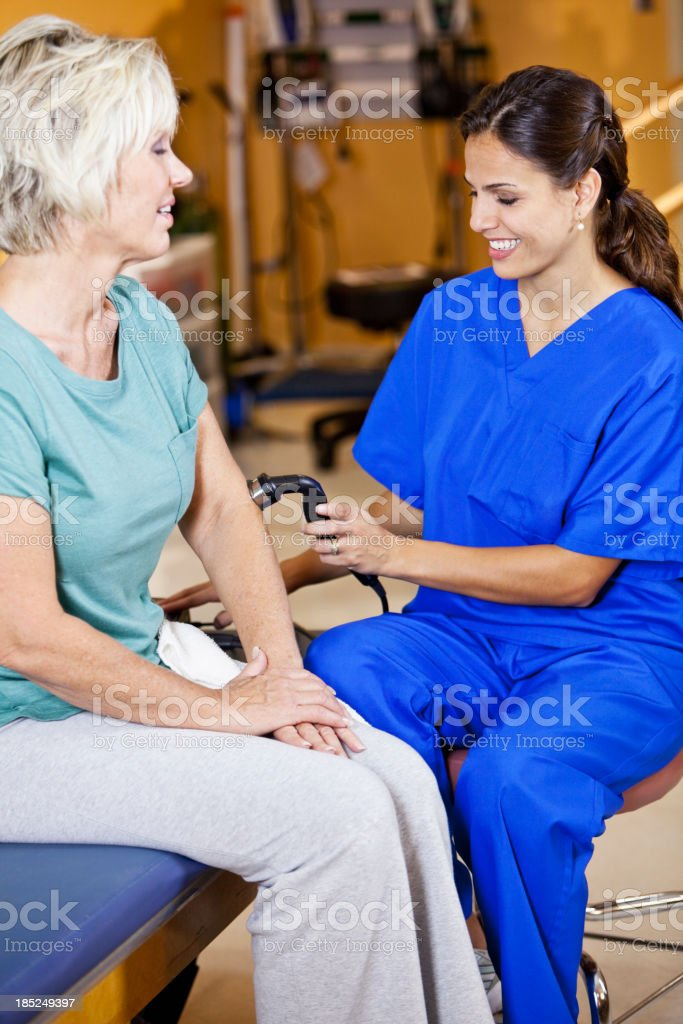 Physical therapist using ultrasonic massager on patient stock photo