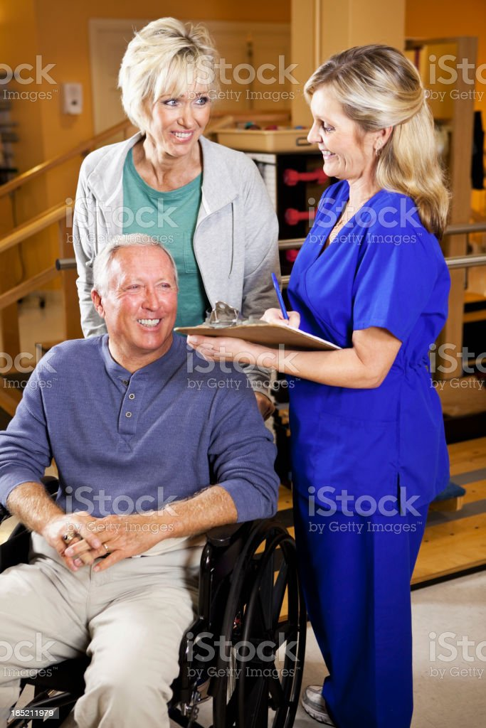 Physical therapist with patient and spouse stock photo