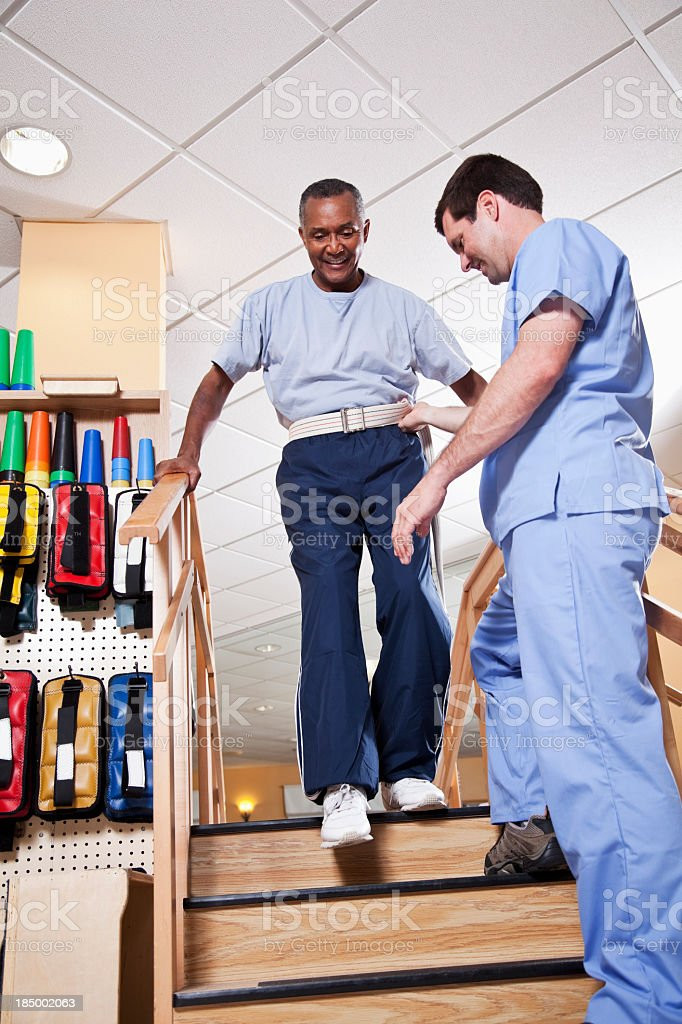 Physical therapist with senior man climbing stairs stock photo