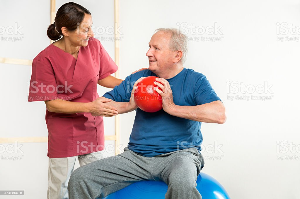 Physical therapist with senior man stock photo