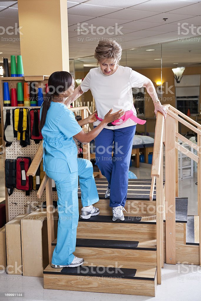 Physical therapist with senior patient on stairs stock photo