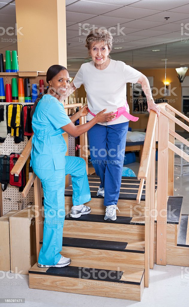 Physical therapist with senior woman climbing stairs stock photo