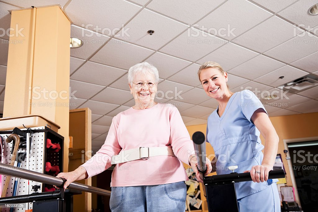 Physical therapist with senior woman, gait training stock photo