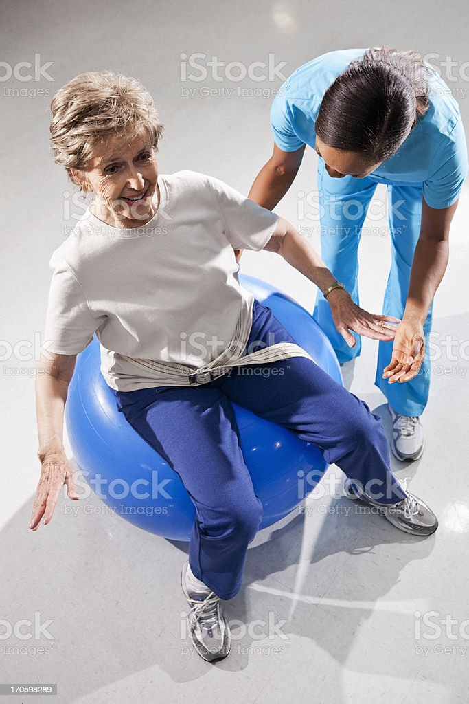 Physical therapist with senior woman on exercise ball stock photo