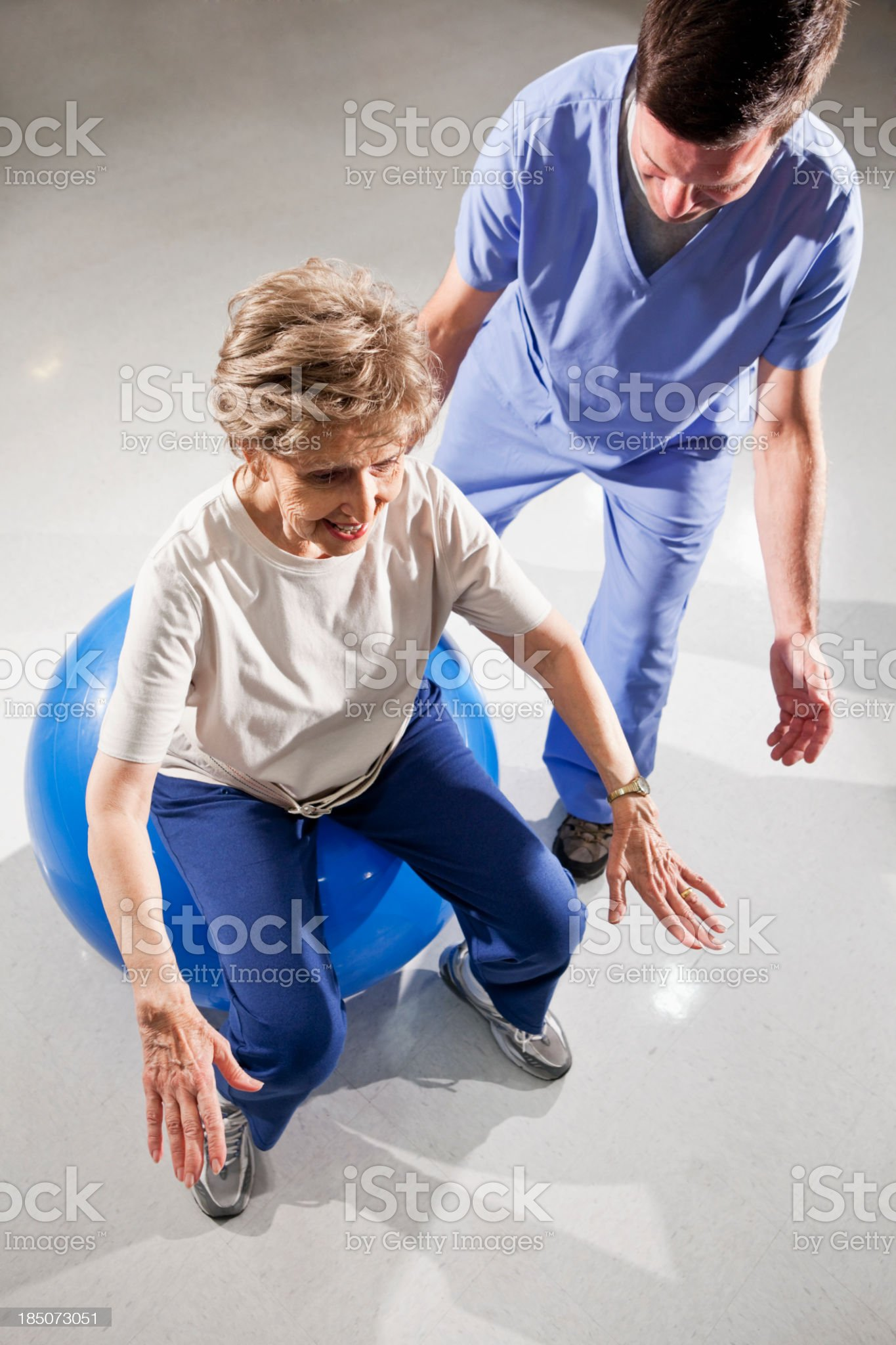 Physical therapist with senior woman on exercise ball royalty-free stock photo
