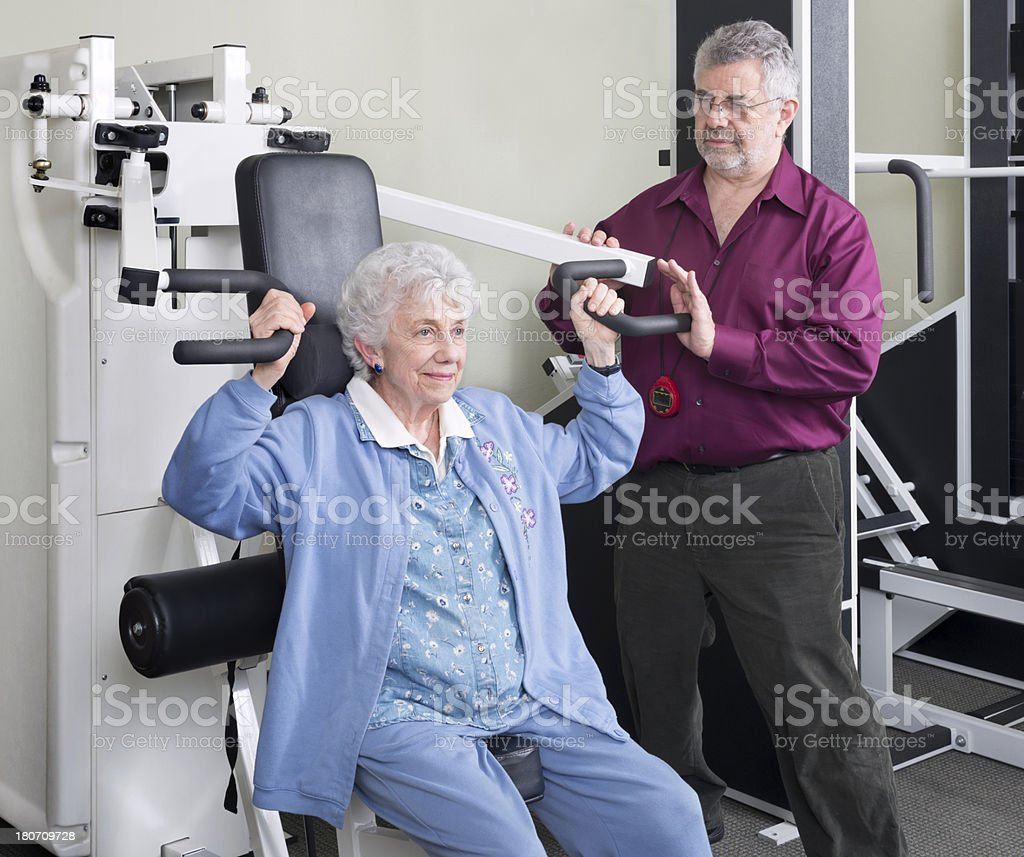 Physical Therapist With Senior Woman On Shoulder Press Machine royalty-free stock photo