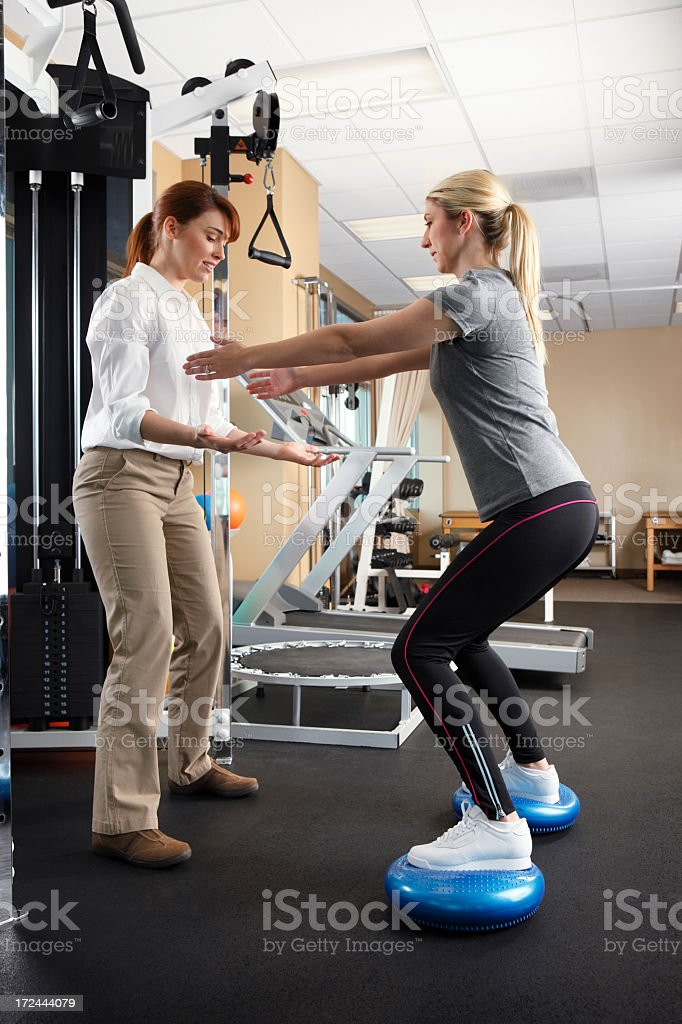 Physical therapist working with a female patient using balance discs royalty-free stock photo