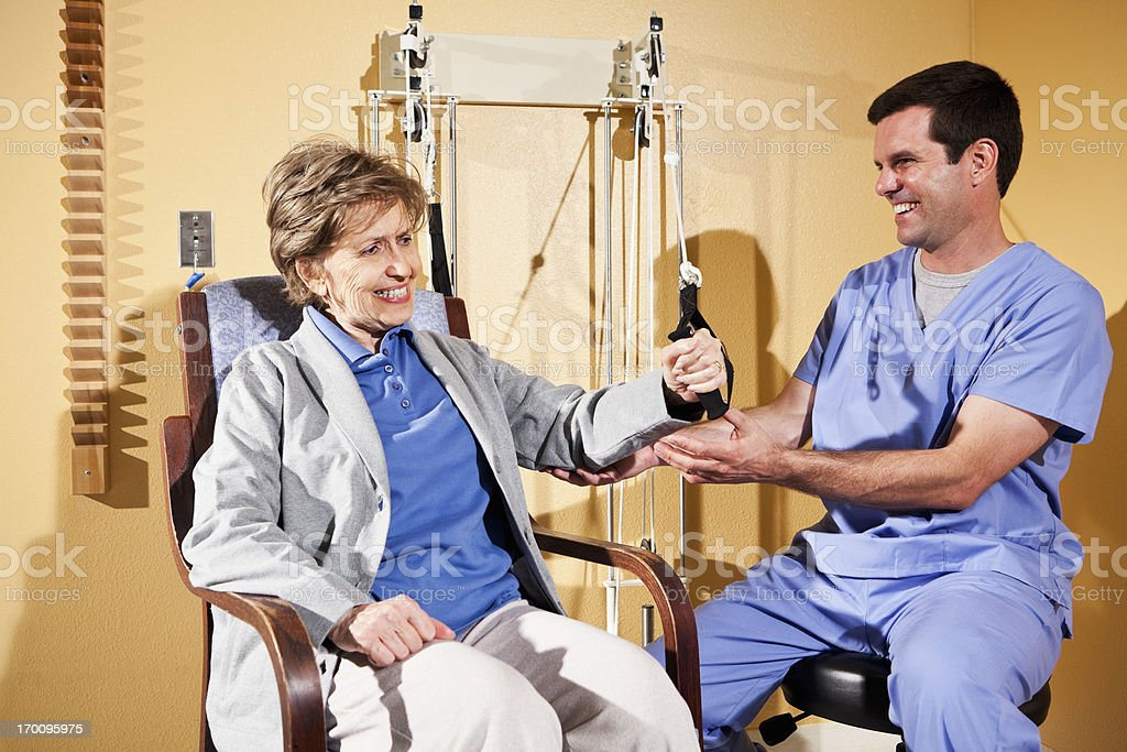 Physical therapist working with patient on upper extremity exerc stock photo
