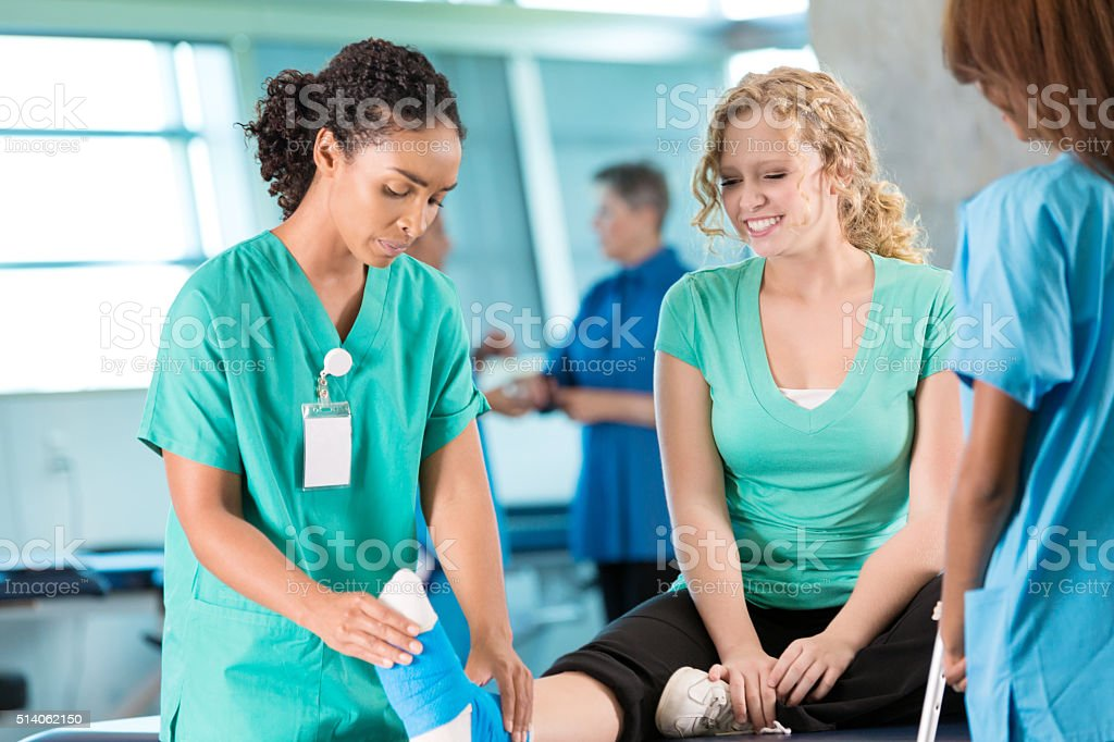 Physical therapist works with young athlete stock photo