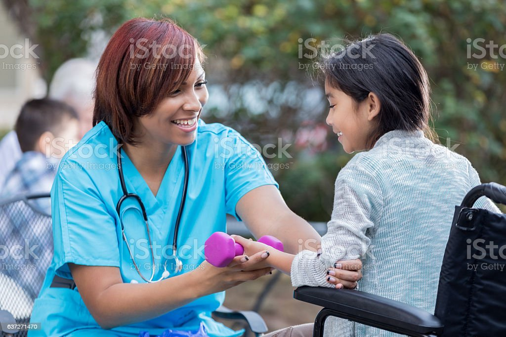 Physical therapist works with young girl in wheelchair stock photo