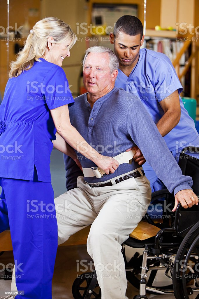 Physical therapists helping patient into wheelchair royalty-free stock photo