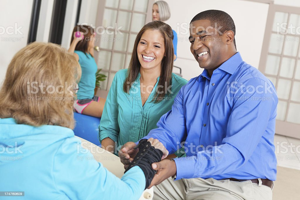 Physical therapists in busy rehabilitation hospital consulting with injured patient stock photo