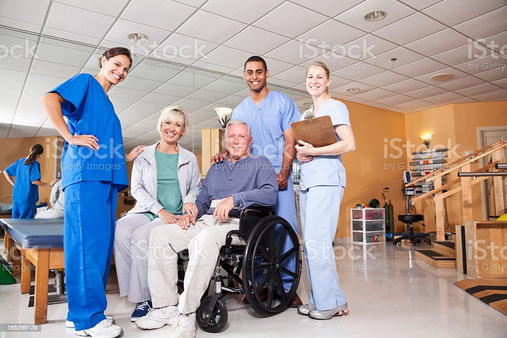 Physical therapists with patient and spouse stock photo