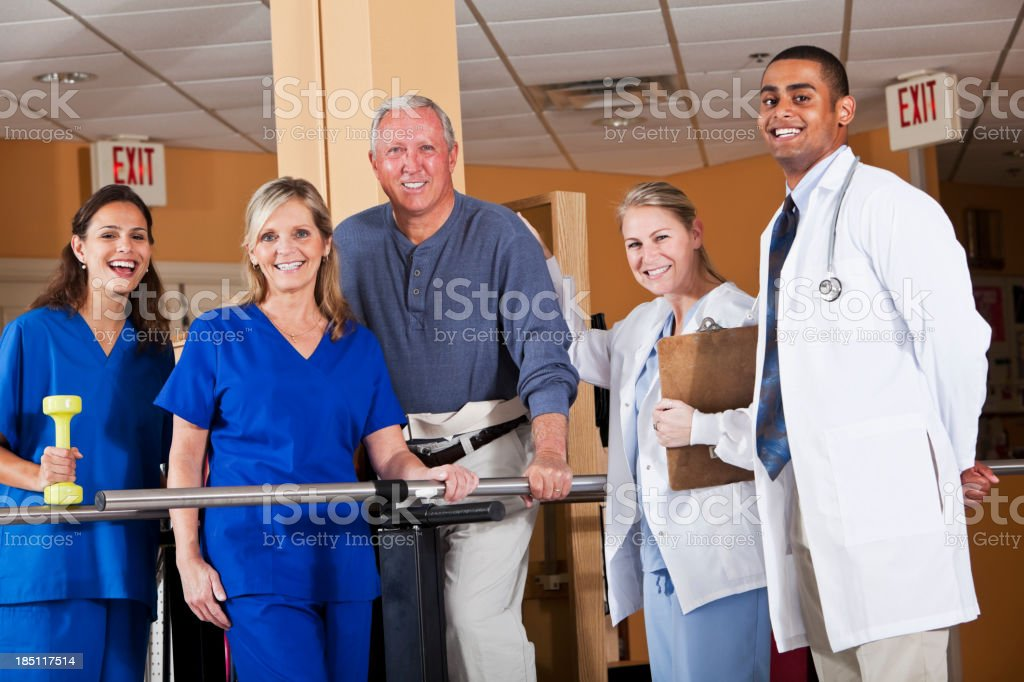 Physical therapy patient with medical staff stock photo