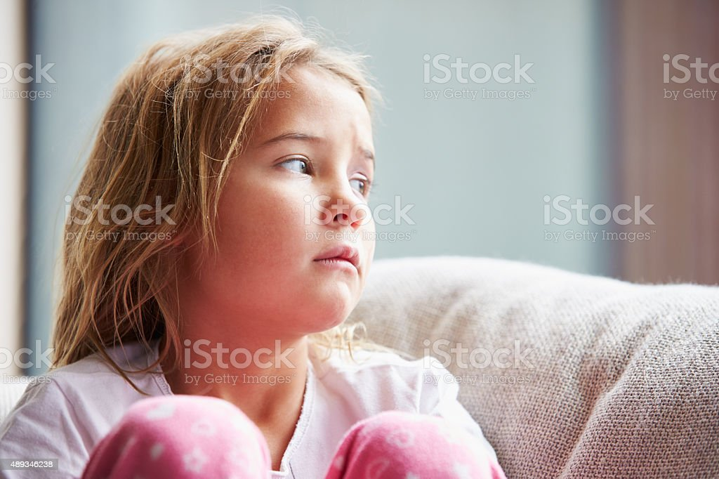 Physically Abused Child At Home Sitting On Sofa stock photo