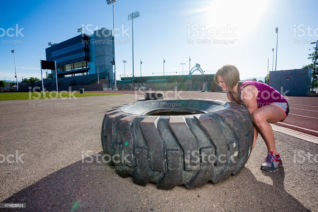 Physically Fit Woman Flipping a Tire for a gym Workout stock photo