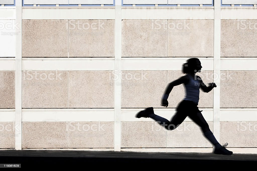 Physically fit woman runs for exercise stock photo