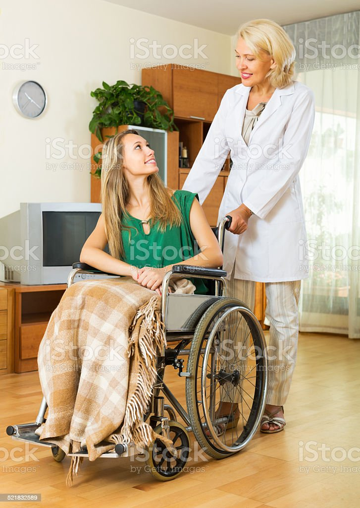 Physician and disabled girl communicating stock photo