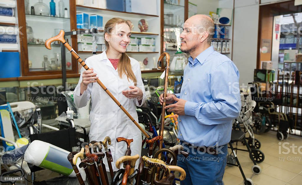 Physician offering cane to customer stock photo