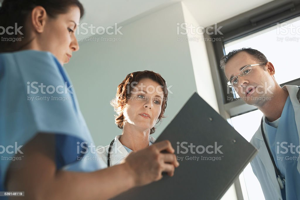 Physicians Reviewing Medical Chart stock photo