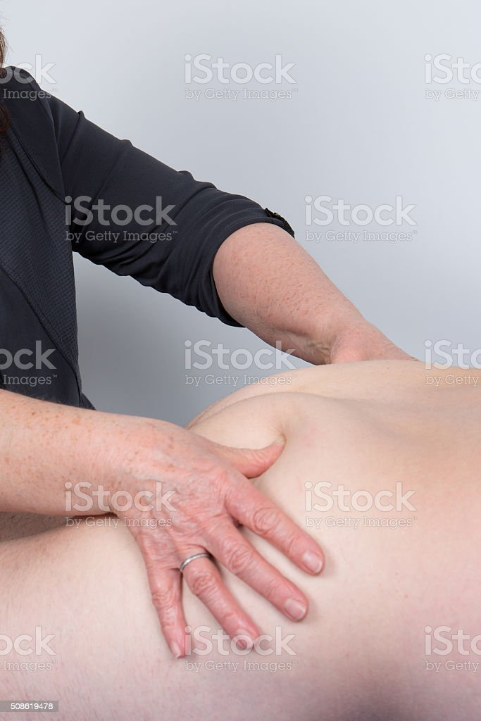 Physio manipulating the buttock of a patient in a room stock photo