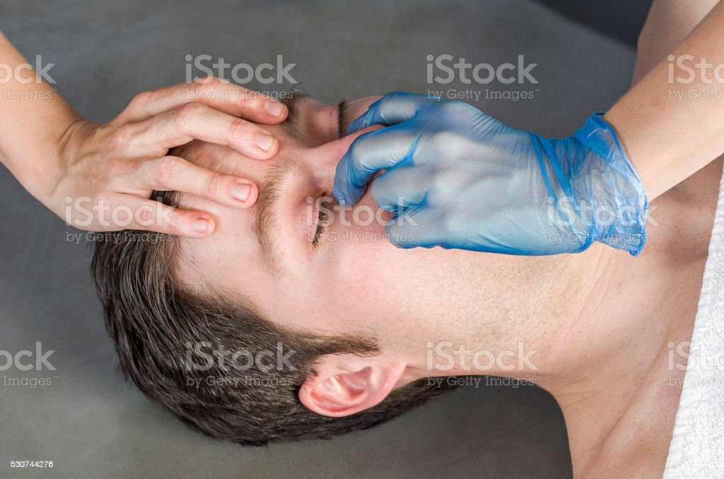 Physiotheraphist doing a sinus massage, theraphy. stock photo