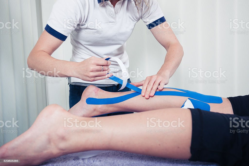 Physiotherapist applying kinesio tape stock photo