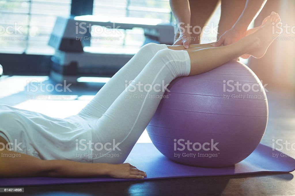 Physiotherapist assisting a patient with exercise ball stock photo