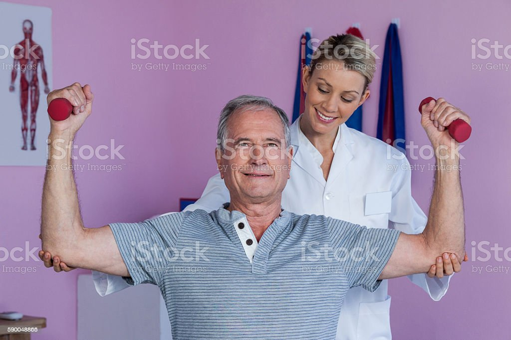 Physiotherapist assisting senior man to lift dumbbell stock photo