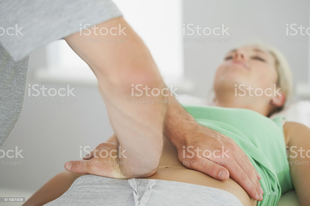 Physiotherapist checking patients pelvis alignment stock photo