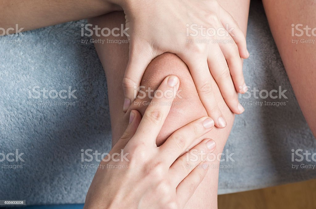 Physiotherapist, chiropractor doing a patellar mobilization, Kne stock photo