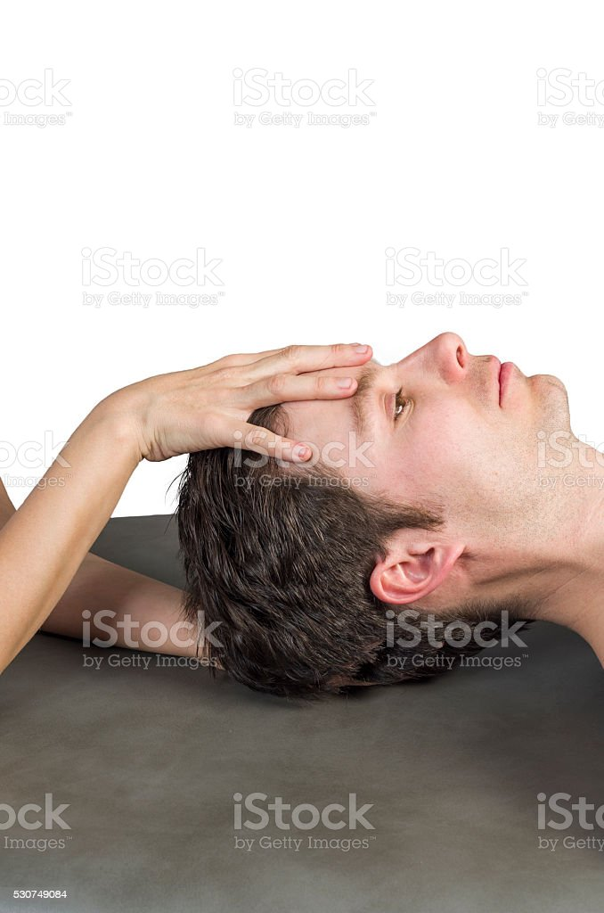 Physiotherapist doing a cranial sacral therapy to a man patient. stock photo