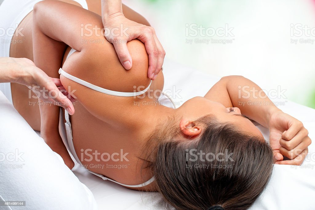 Physiotherapist doing healing treatment on female shoulder blade stock photo