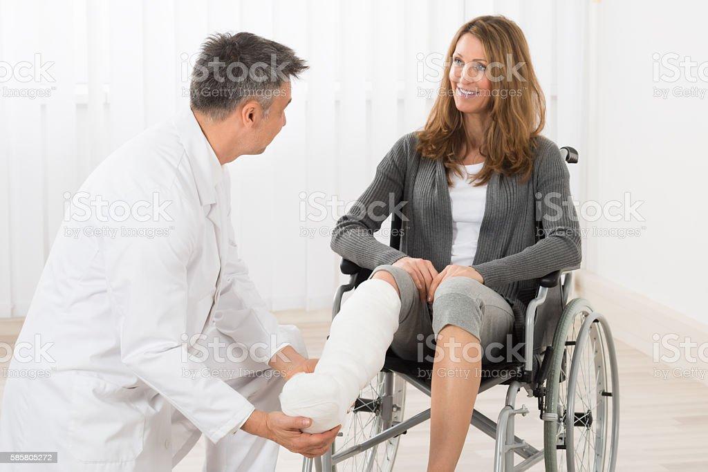 Physiotherapist Examining Leg Of Patient stock photo