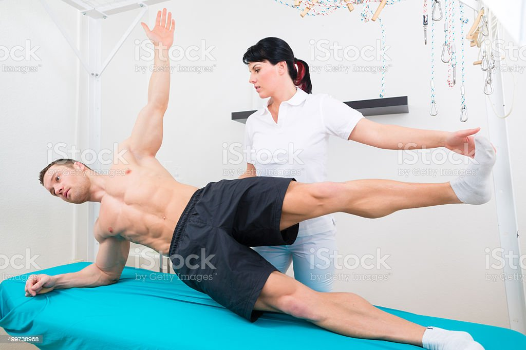 Physiotherapist exercising with patient in practice stock photo