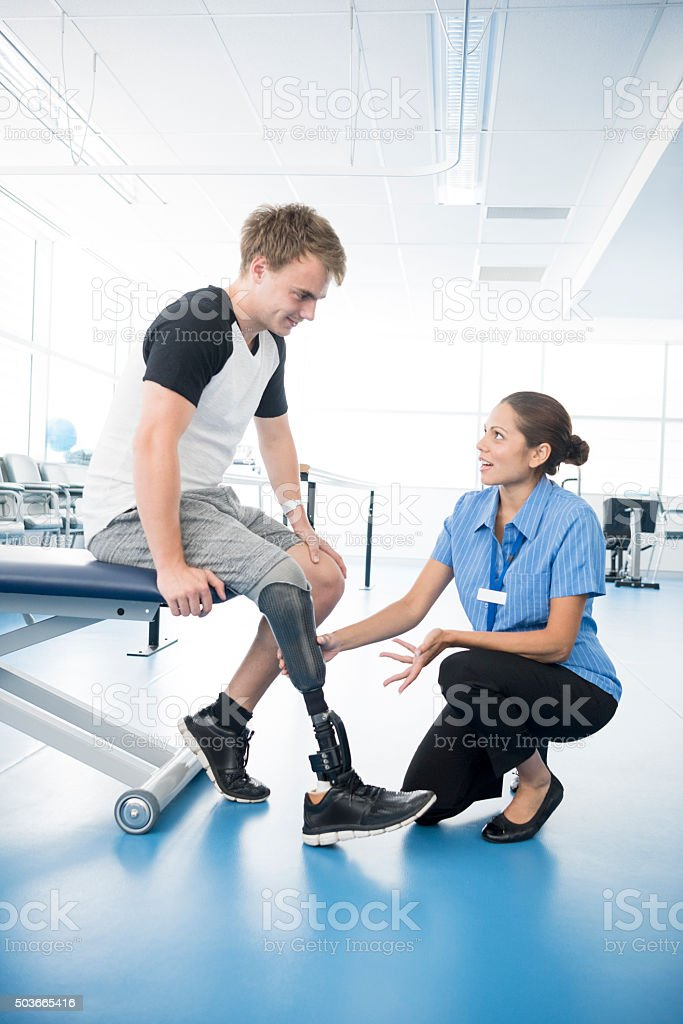 Physiotherapist explaining to young man with prosthetic leg stock photo