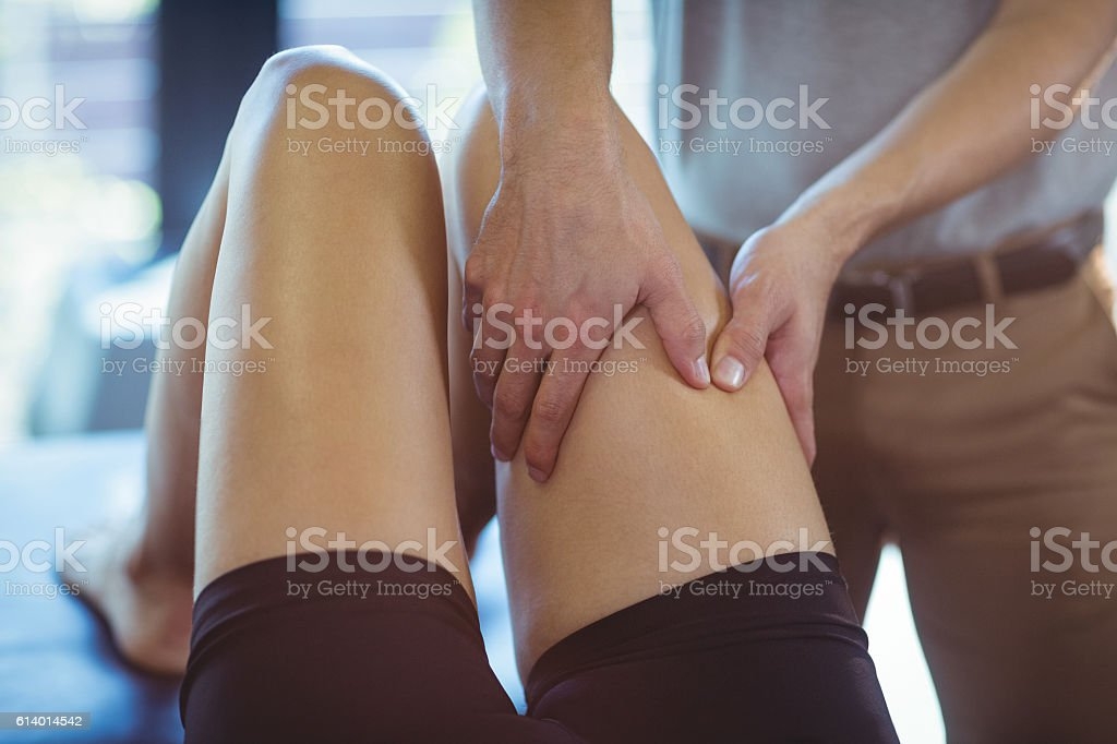 Physiotherapist giving leg massage to a woman stock photo