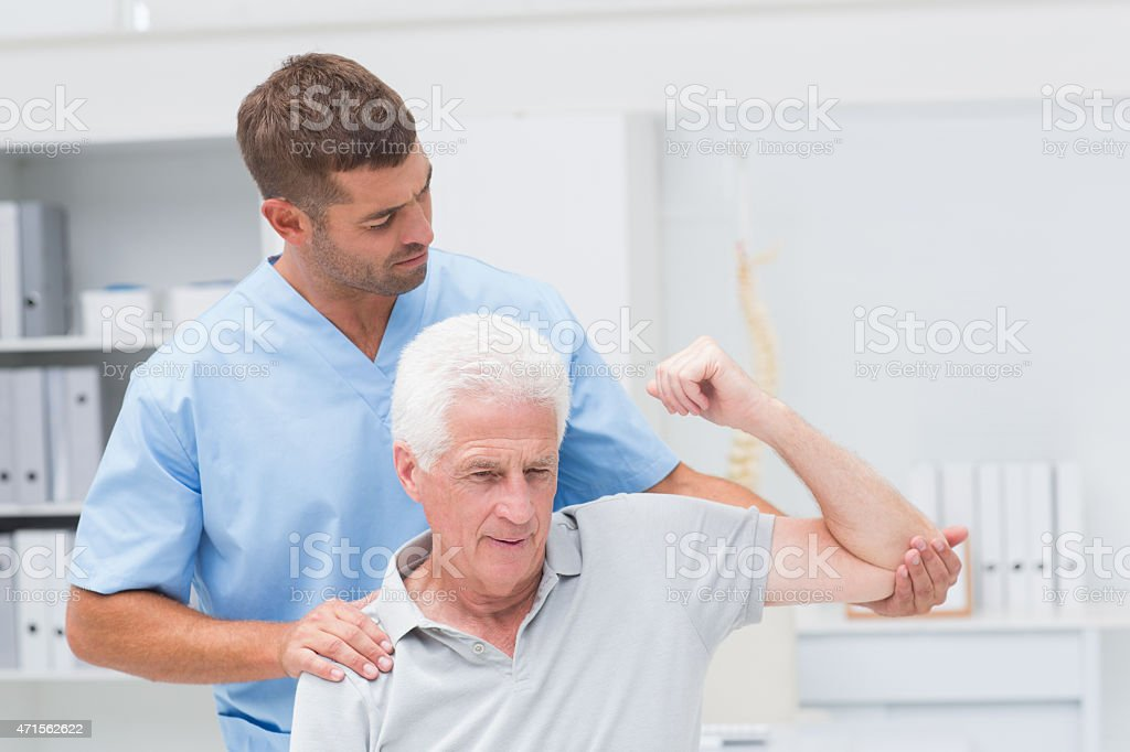 Physiotherapist giving physical therapy to man stock photo