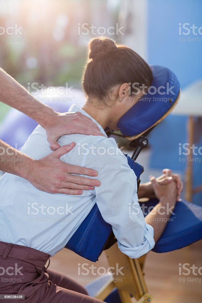 Physiotherapist giving shoulder massage to a female patient stock photo