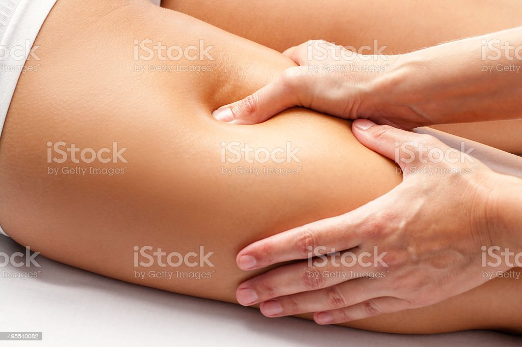 Physiotherapist hands massaging hamstring on athlete. stock photo