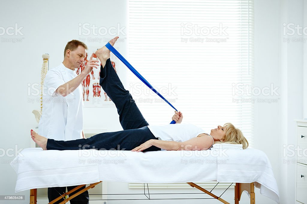 Physiotherapist helping his patient stretching in medical office stock photo