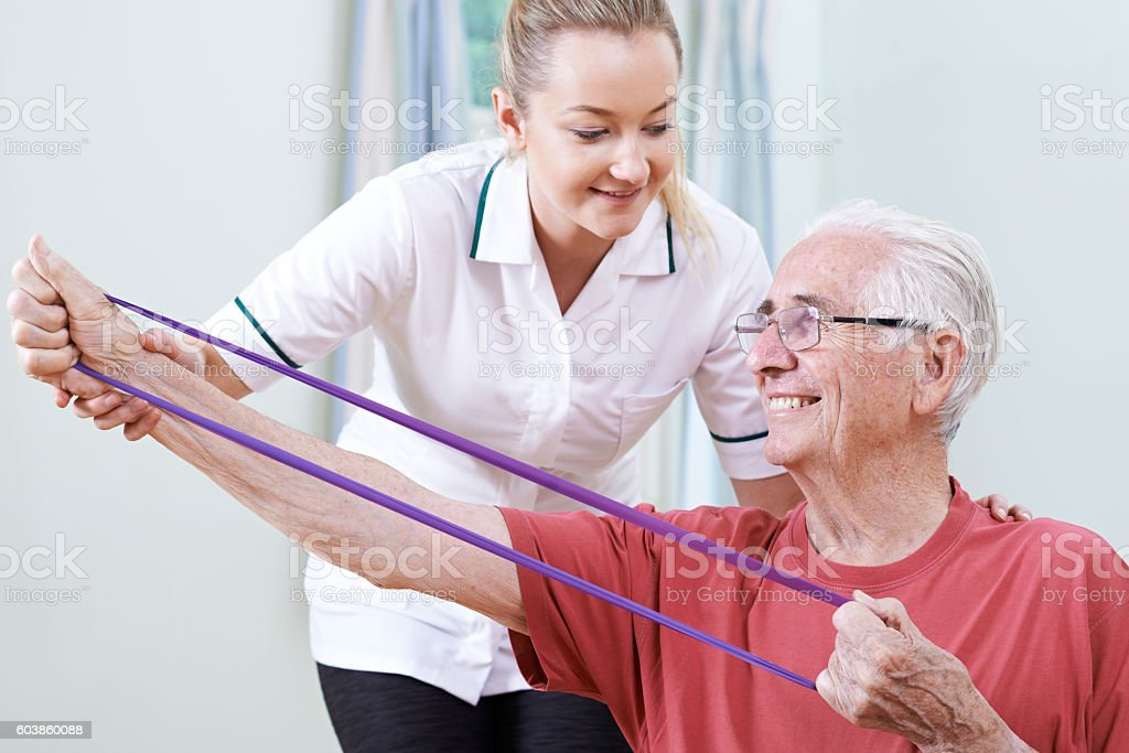 Physiotherapist Helping Senior Male To Use Resistance Band stock photo