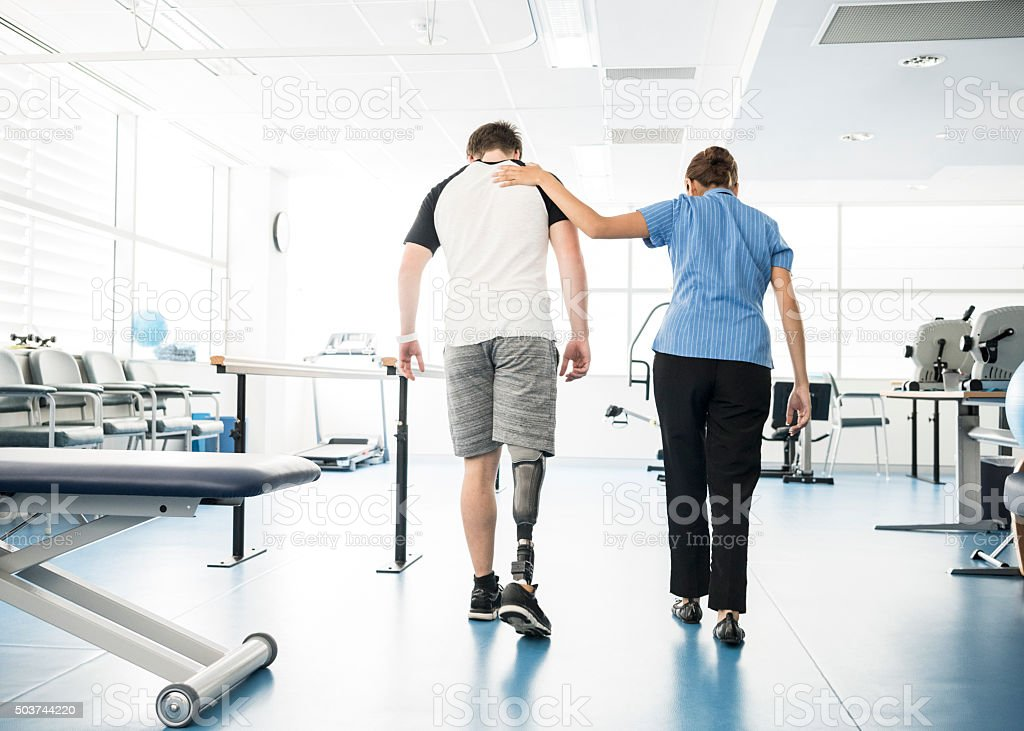 Physiotherapist helping young man with prosthetic leg stock photo