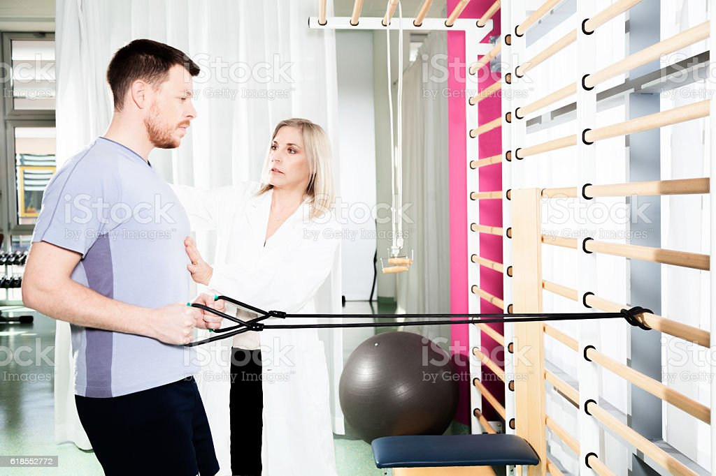 physiotherapist helps a patient to restore movement stock photo