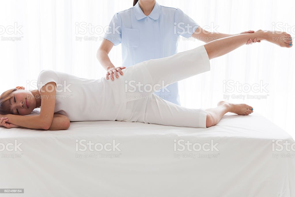 Physiotherapist massaging leg of young woman at spa stock photo