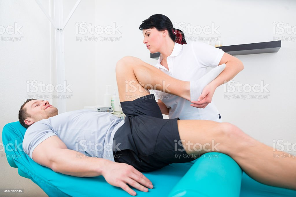 Physiotherapist medicate patient in practice stock photo