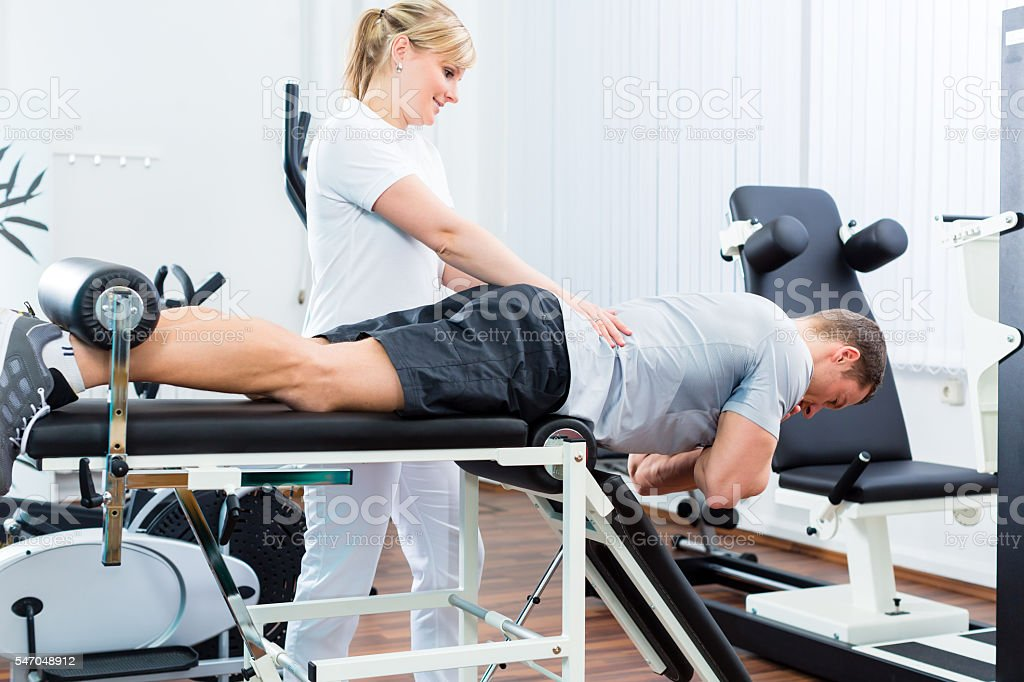 Physiotherapist or sport doctor with patient stock photo