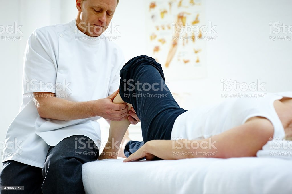 Physiotherapist working on woman's lower leg stock photo
