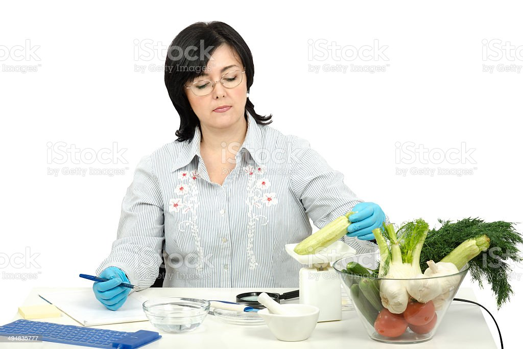 Phytocontrol technician weighing a zucchini stock photo
