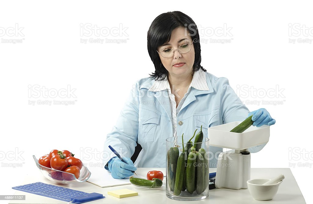 Phytosanitary technician weighing cucumber royalty-free stock photo